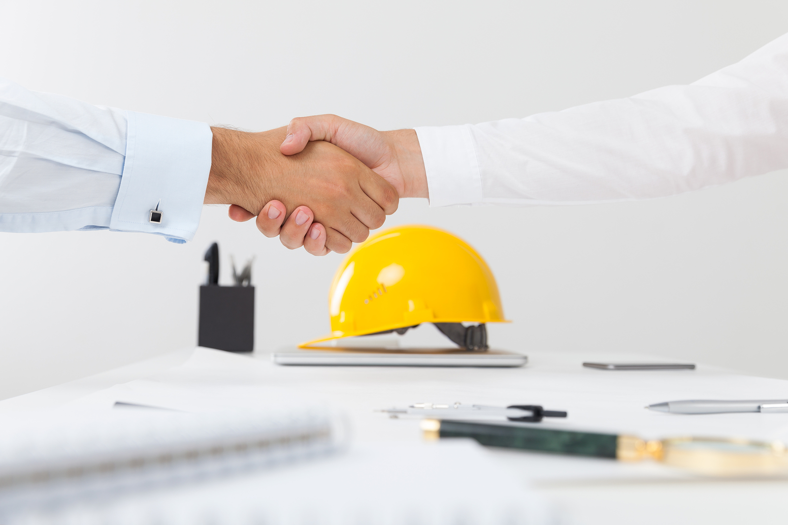 Close up of a handshake and a yellow builder helmet is in the background.