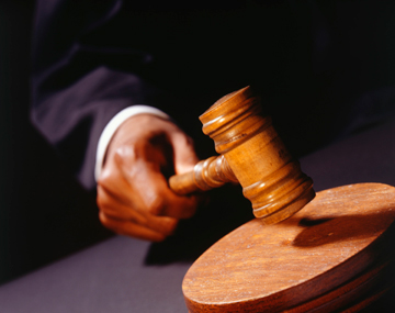 Close up of a wooden gavel strucking a wooden block by a hand.